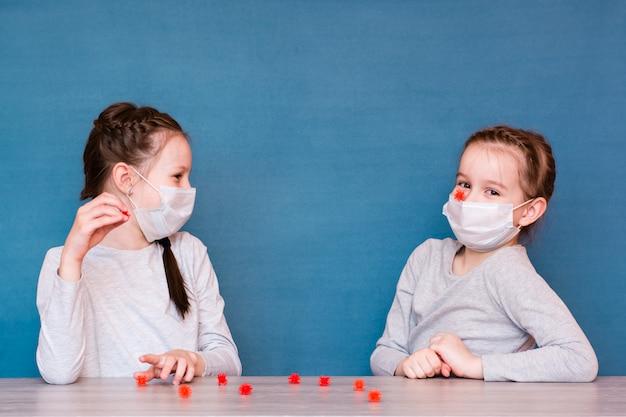 検疫の医療用マスクを着た女の子はウイルスを再生します。流行に孤立した子供たちを楽しませる