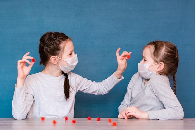 検疫の医療用マスクを着た女の子はウイルスを再生します。流行時に孤立した子供の余暇