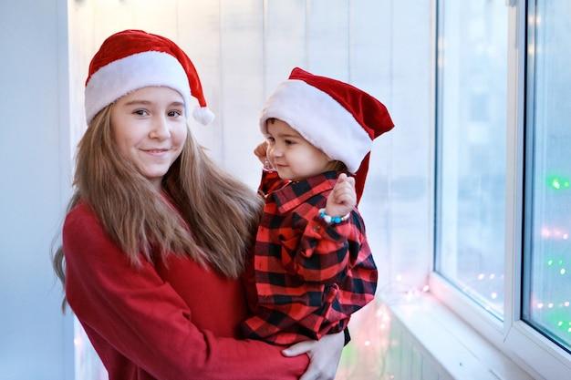빨간 산타 모자에있는 여자. 크리스마스 의상 자매.