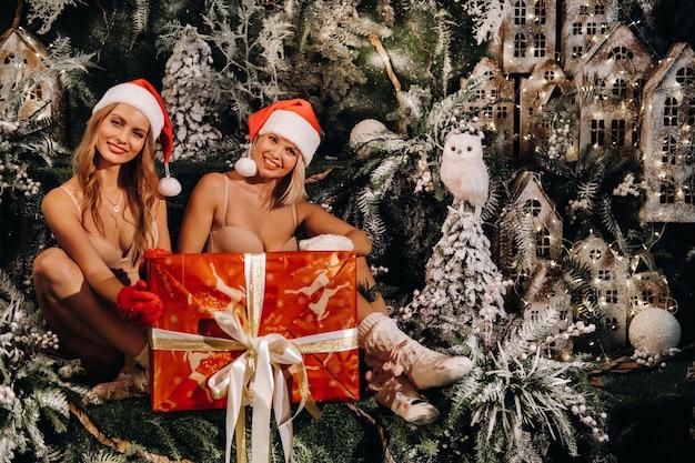 멋진 크리스마스 배경에 손에 큰 크리스마스 선물을 들고 산타클로스 모자를 쓴 소녀들. 크리스마스 나무와 작은 집 배경에 수영복을 입은 웃는 여성