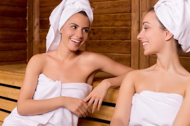 Девушки в сауне. две привлекательные женщины, завернутые в полотенце, разговаривают друг с другом и улыбаются во время отдыха в сауне