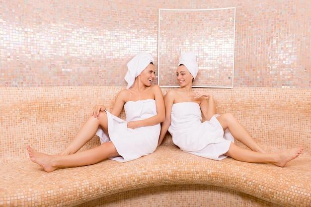 Девушки в сауне. две привлекательные молодые женщины, завернутые в полотенце, разговаривают друг с другом и улыбаются, проводя время в сауне