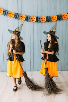 Girls in sorceress clothes holding broomsticks