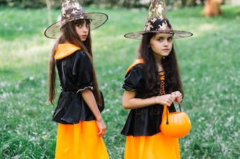 Girls in sorceress costumes poising in park