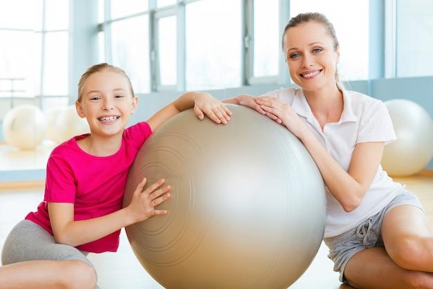 스포츠 클럽의 소녀들. 쾌활한 엄마와 딸이 피트니스 공에 기대어 스포츠 클럽 바닥에 앉아 웃고 있다