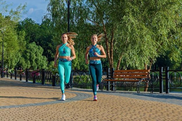 スポーツロンパースの女の子はウォームアップして走ります。路上でのフィットネス。スポーツの分野で運動をしている魅力的な女の子。フィットネスのためのスポーツウェア。ループを使ったフィットネスエクササイズ。健康的な生活様式。