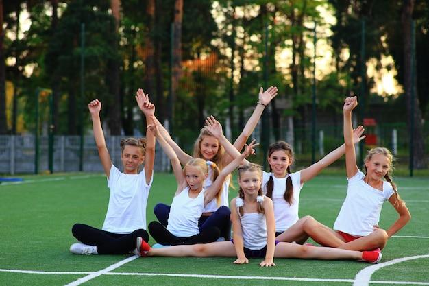 スポーツウェアの女の子が遊び場に座っています。