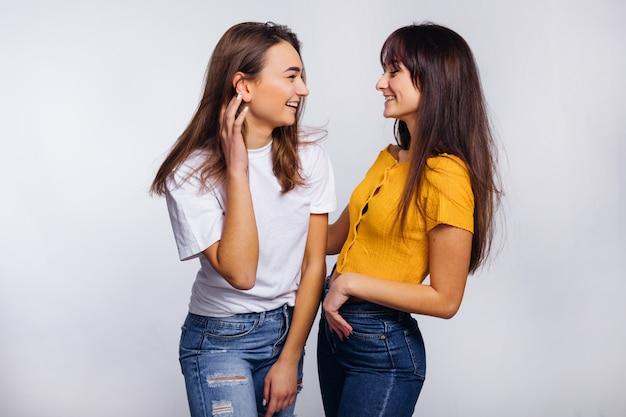 スタジオでおしゃれなジーンズを着た女の子が楽しい。友達。お互いを見てください。