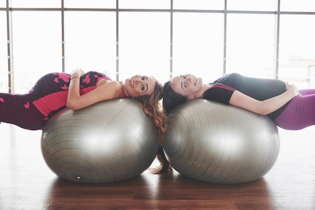 Девушки в тренажерном зале лежат на двух мячах для стабилизации во время беременности и улыбаются.