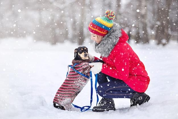 Девушки в теплых куртках и шапках играют в зимнем парке с собакой на прогулке