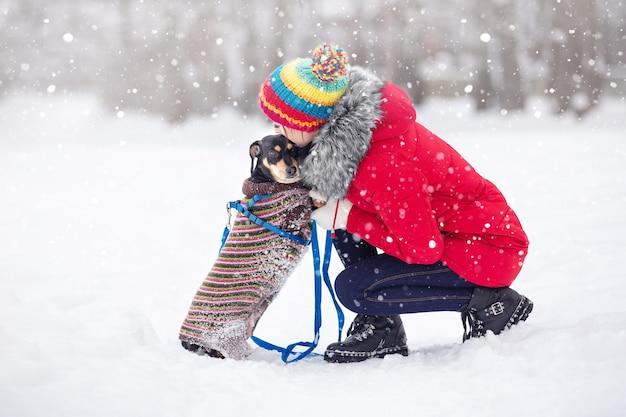 暖かいジャケットと帽子をかぶった女の子が散歩で犬と一緒に冬の公園で遊ぶ