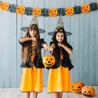 Девушки в одежде ведьм делают вид, что держат ножи шеи