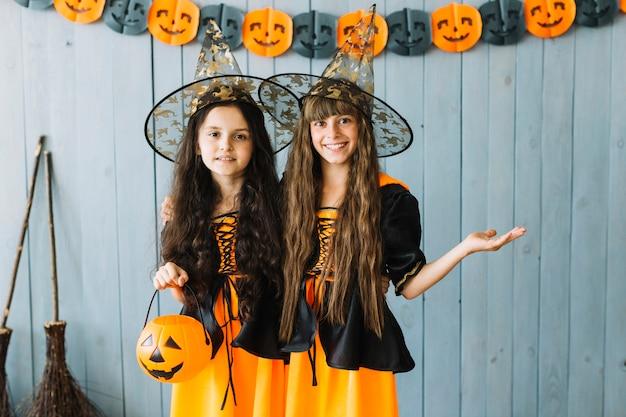 Девушки в одежде ведьм, стоя в остроконечных шляпах и улыбающихся