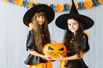 Girls in witch costumes holding pumpkin together