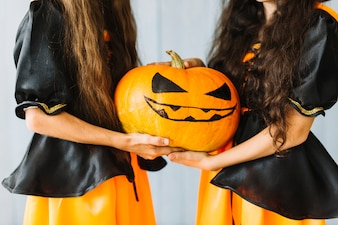 Girls in witch costumes holding together halloween pumkin