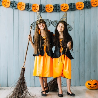 Girls in witch costumes hugging and holding broomsticks