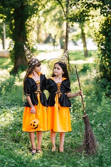 Девушки в костюмах ведьмы обнимаются и смотрят друг на друга