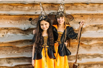 Girls in witch costumes hugging and smiling