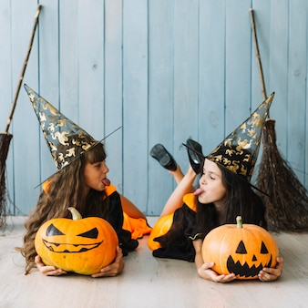 Girls in witch costumes lying putting out tongues