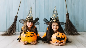 Girls in witch costumes lying with pumpkins