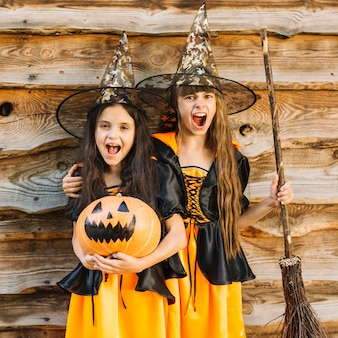 Girls in witch costumes making faces holding broomstick and pumpkin