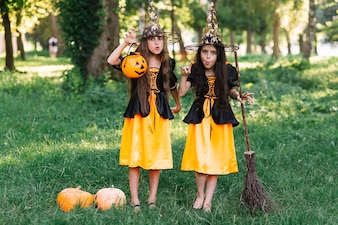 Girls in witch costumes making faces, holding broomstick and pumpkin
