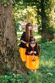 Девушки в костюмах ведьмы позируют возле дерева