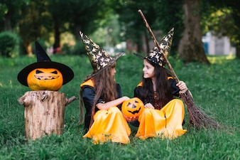 Girls in witch costumes sitting on grass, looking at each other