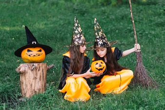 Girls in witch costumes sitting on grass, looking at pumpkin