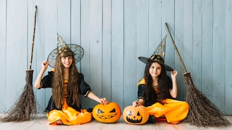 Girls in witch costumes sitting with pumpkins and brooms