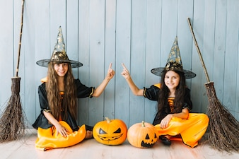Girls in witch costumes with brooms sitting by fence