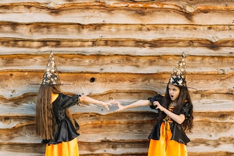 Girls in witch costumes with reach out hands looking each other