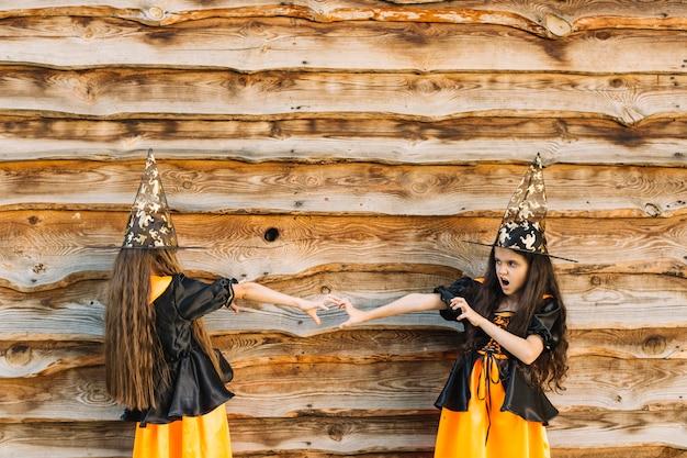 마녀 의상을 입은 소녀들은 손을 서로 뻗어