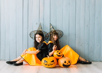 Girls in witch suits and pointy hats sitting on floor with pumpkins