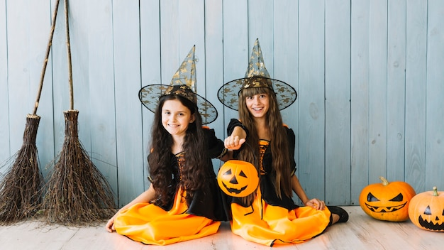 Девочки в колдунья, сидя на полу, холдинг хэллоуин корзины и улыбается
