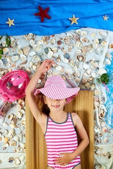 The girls is lying on a fictional beach near the sea or ocean, sunbathes.