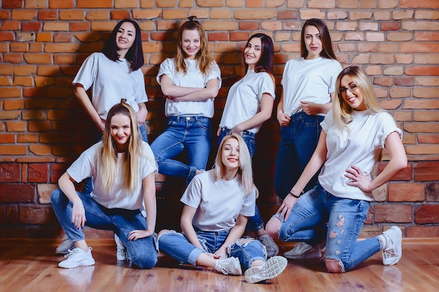 Girls in jeans at background of brick wall