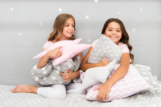 여자 아이들은 귀여운 베개를 껴안습니다. 껴안고 싶은 귀여운 어린이 베개. 장식용 베개를 찾아 방에 재미를 더하세요. 행복한 어린 시절의 아늑한 집. 당신의 아이 방을 위한 사랑스러운 쿠션.