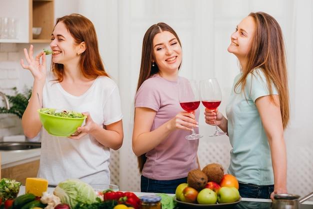 여자 부엌 파티. 즐거운 요리 레저. 와인을 마시고 샐러드를 먹는 여성.