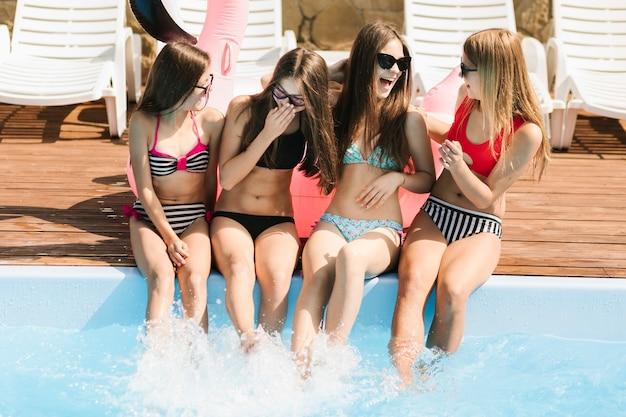 Девушки смеются друг у друга в бассейне