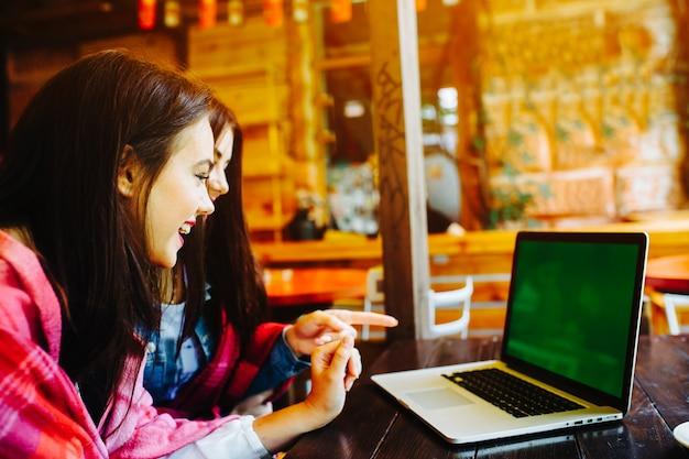 Девушки, смеясь, они смотрят на ноутбук