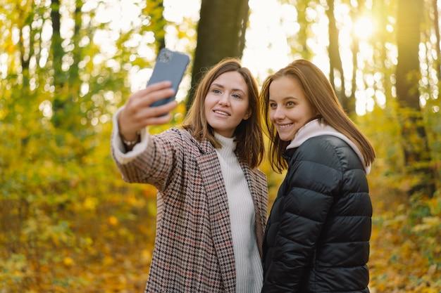 소녀들은 라이프스타일 이동성의 개념으로 웃고 셀카를 찍는다.