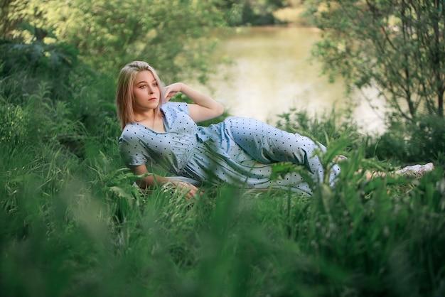 湖の近くの草に横たわっている女の子。夏、自然