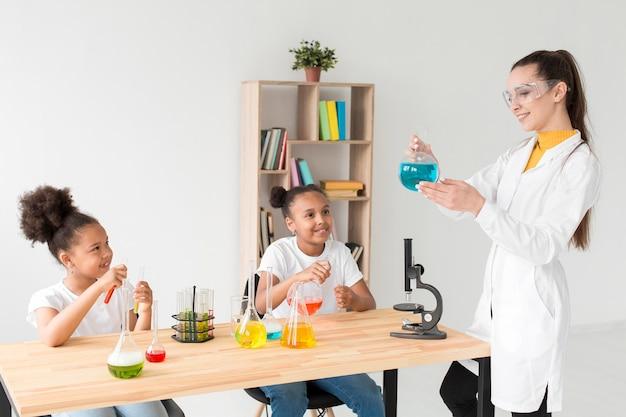 Девочки изучают науку от женского ученого, держащего зелье