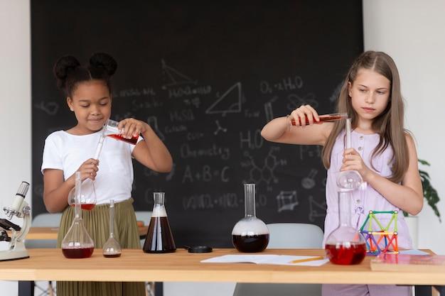 수업 시간에 화학에 대해 더 많이 배우는 소녀들