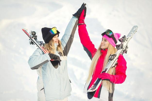 女の子たちは雪の中でスキーをしました。写真を撮られるのを楽しんでいます。山で時間を過ごします。