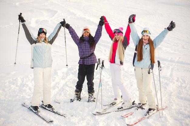 Le ragazze hanno lasciato lo sci nella neve. divertirsi a farsi fotografare. trascorri del tempo in montagna.