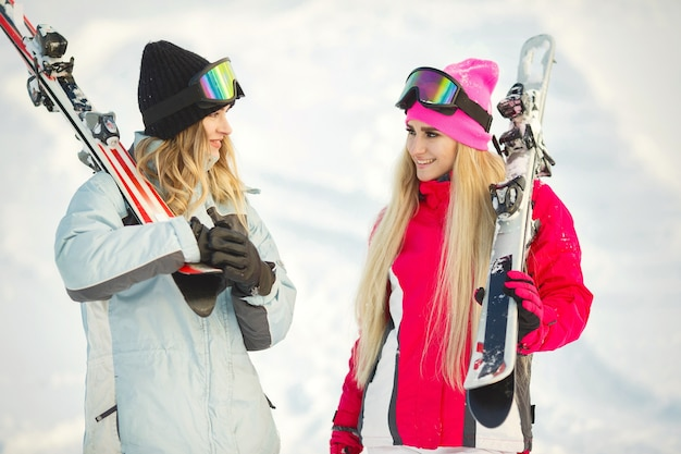 Girls left skiing in snow. having fun on being photographed. spend time in mountains.