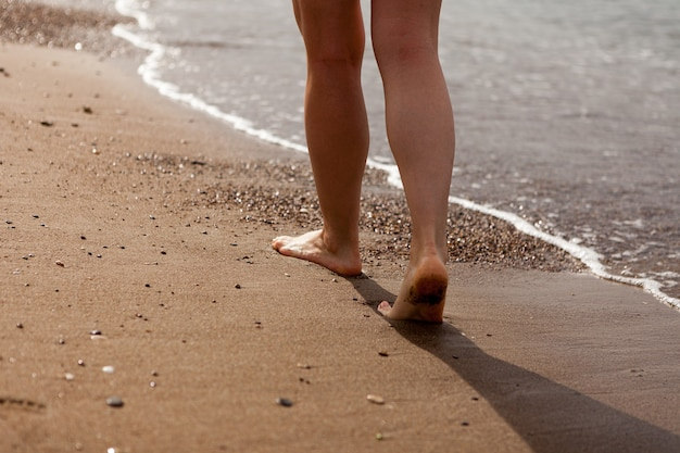 The girls legs close up barefoot on the sand and the sea shore a girls feet a woman walks along the ...