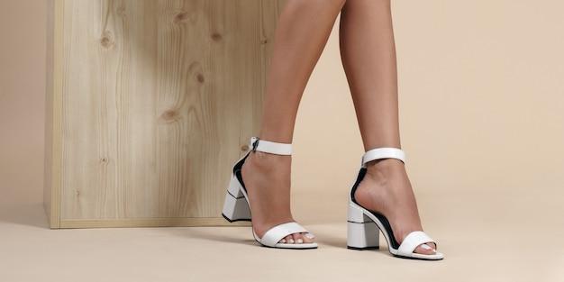 Ноги девушки в белых босоножках на высоких каблуках и танкетке на бежевом